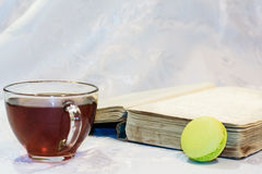 Tea in a glass cup, old book on a white background. A cup of black tea next to an old book and a dessert macarons on a white background Royalty Free Stock Images