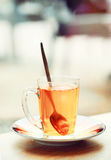 Tea in glass cup on saucer at street cafe table Royalty Free Stock Photo