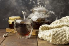 Tea in glass cup with teapot and knitted blanket near, with jam in jar at wood background, with spoon near. royalty free stock photo
