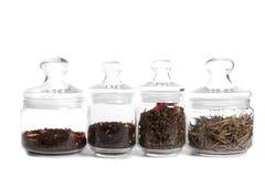 Tea in glass jars: milk puer, indian tea, oolong. ITea in glass jars: (from left to right) milk puer, aromatized indian tea, oolong with rose, white tea (silver Stock Photos