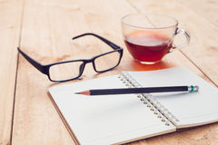 Tea in glass and notebook,pencil with glasses Stock Photo