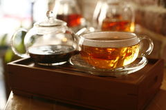 Tea in glass teacup. Clear glass teapot and teacup with tea,  arranged on a bamboo tray Royalty Free Stock Photos