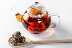 Tea in a glass teapot with a blooming large flower. Teapot with exotic green tea on a white background with dried balls-buds for. Tea brewing royalty free stock photo