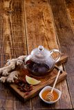 Tea in a glass teapot with rosehip honey and ginger. Space under the text royalty free stock image