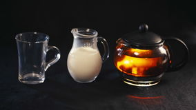 Tea in a glass teapot, the tea in a transparent Cup and a small jug of milk.  stock video
