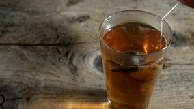 Tea in a glass wooden table. Man pours tea in a glass cup, on a wooden table stock video