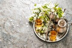 Tea glasses pot Oriental silver tableware Spring flowers decorat Royalty Free Stock Image