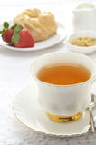 Tea with glazed cruller and strawberries royalty free stock photo