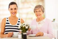 Tea with grandmother. Beautiful young women having tea with grandmother or mother Royalty Free Stock Photos