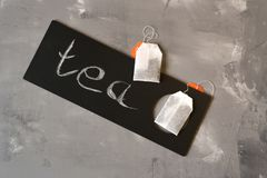 Tea on a gray background and a black sign and the inscription: Tea. Tea bags on a gray background and a black plate with the inscription: Tea royalty free stock photo