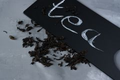 Tea on a gray background with a black sign and the inscription: Tea. Tea leaves on a gray background with a black plate and the inscription: Tea stock photo