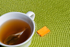 Tea With Green. Cup of tea with bag and green placemat Stock Photos