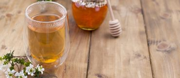 Tea with herbs and honey on a wooden background and flowers. Natural health. Copy cpace. Long format. Banner stock images