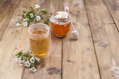 Tea with herbs and honey on a wooden background and flowers. Natural health. Copy cpace.  Stock Images