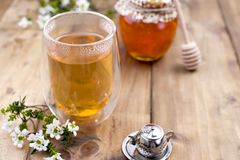 Tea with herbs and honey on a wooden background and flowers. Natural health. Copy cpace stock photos