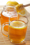 Tea with honey. Cup of tea with lemon and honey Royalty Free Stock Image