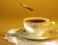 Tea and Honey. A hot cup of tea with a touch of honey... comfort in a cup royalty free stock image