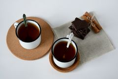 Tea in an iron mug and chocolate on white background stock photography