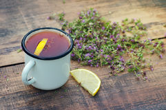Tea in an iron mug, lemon, medicinal herbs. On a wooden surface Royalty Free Stock Photography
