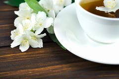 Tea with jasmine in a white cup on a wooden table. Tea with jasmine in a white cup on a saucer on a wooden table. Jasmine flower Stock Photography