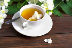 Tea with jasmine in a white cup on a wooden table. Tea with jasmine in a white cup on a saucer on a wooden table. Sprinkled Jasmine Flower Petals Stock Images