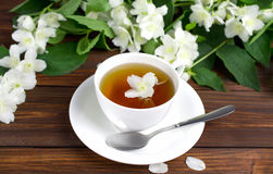 Tea with jasmine in a white cup on a wooden table. Tea with jasmine in a white cup on a saucer on a wooden table. Sprinkled Jasmine Flower Petals Royalty Free Stock Images