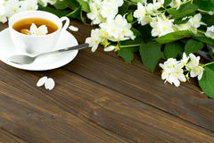 Tea with jasmine in a white cup on a wooden table. Tea with jasmine in a white cup on a saucer on a wooden table. Sprinkled Jasmine Flower Petals Royalty Free Stock Image