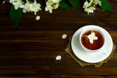 Tea with jasmine in a white mug on a wooden table. Tea with jasmine in a white cup on a saucer on a wooden table. Sprinkled Jasmine Flower Petals Royalty Free Stock Photography