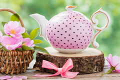 Tea kettle and basket with pink wild roses. Stock Photo