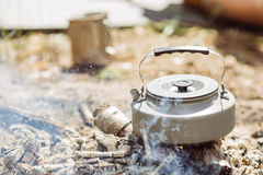 A tea kettle boiling over an open fire Stock Photography