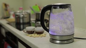 Tea kettle with boiling water. Tea bags and sugar on the background