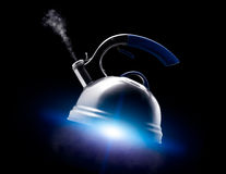 Tea kettle with boiling water on black background. Stock Photos