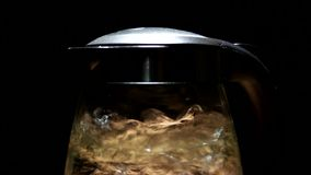 Tea kettle with boiling water on a black background stock footage