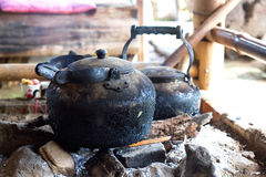 Tea kettle with boiling water on fire wood royalty free stock image