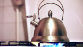 Tea kettle with boiling water on gas stove stock footage