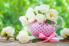 Tea kettle and bouquet of roses. Stock Photos