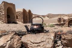 Tea kettle on campfire in iranian desert Dasht-e. Royalty Free Stock Image