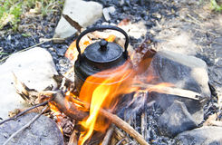 Tea kettle on fire. Tea kettle on camping fire stock image
