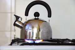Tea kettle on a flaming gas stove. Stock Photography