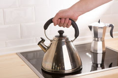 Tea kettle in hand on black stove Royalty Free Stock Photos