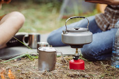 A tea kettle on a propane stove next to a metal cup Royalty Free Stock Images