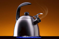 Tea Kettle with Steam Over A Hot Gas Stove Stock Images