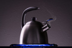 Tea Kettle with Steam Over A Hot Gas Stove Stock Photography