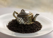 Tea leaf black on a white ceramic saucer with a metal teapot. Close-up Stock Image