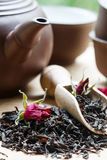 Tea leaves and buds of roses, teapot and cups on the table Royalty Free Stock Photo