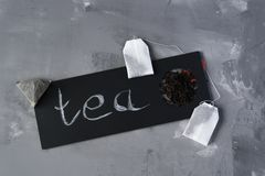 Tea on a gray background and a black sign and the inscription: Tea. Tea leaves on a gray background with a tea bag and a black sign and the inscription: Tea stock image