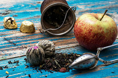 Tea leaves and red apple on wooden background Royalty Free Stock Images