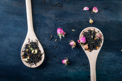 Tea leaves with rose buds in wooden spoons Stock Photos
