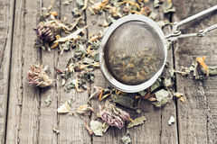 Tea leaves with a tea strainer Royalty Free Stock Photos