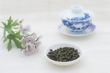 Tea leaves with teacup and flowers Royalty Free Stock Photo